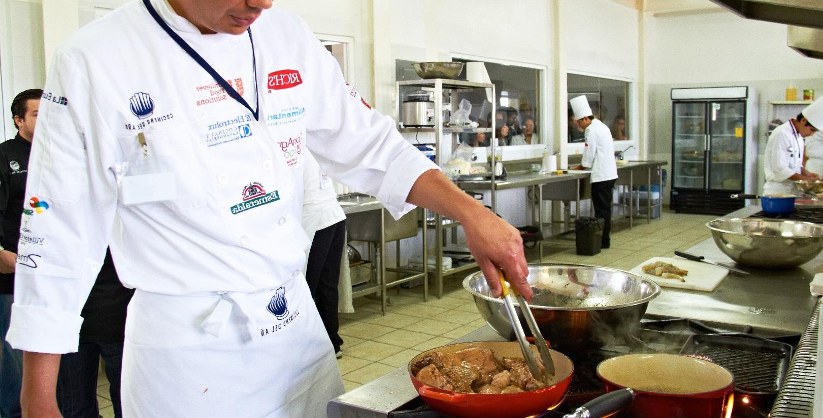 cocinero con vestuario de chef, gorro, chaqueta, delantal, haciendo un pollo
